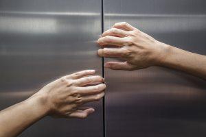 Hände versuchen Fahrstuhltür zu öffnen